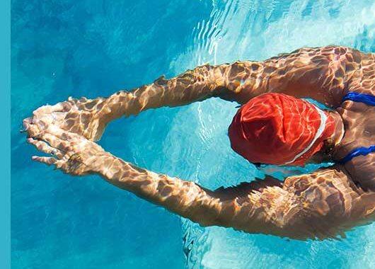 Las piscinas son el refugio favorito de muchas personas para disfrutar del verano. Sin embargo, cuando su mantenimiento no se realiza de manera adecuada o se acude a ellas con frecuencia, se puede producir una indeseable irritación y picor de ojos. ¿Qué función tiene el cloro en las piscinas? Para mantener correctamente una piscina, se requiere un nivel de pH adecuado, similar al de nuestra piel. Así evitamos que el agua sea demasiado ácida y produzca irritación, a la vez que permitimos que los desinfectantes actúen de forma adecuada eliminando virus, bacterias y microorganismos indeseados. Entre los desinfectantes más habituales se encuentra el cloro, que puede administrarse directamente o producido a partir de agua salada. El problema con este producto químico es que, al mezclarse con el material orgánico del agua (nitritos fundamentalmente, como por ejemplo: restos de sudor, orina, etc.), da lugar a un compuesto denominado cloramina. Esta sustancia es la responsable de irritar nuestras mucosas, nuestra piel y principalmente nuestros ojos. El riesgo de irritación es directamente proporcional a los restos orgánicos que se hayan depositado en el agua y a la concentración de cloro administrada. Es decir, cuanto más cloro añadamos porque creemos que más desinfección se requiere, más cloraminas se producirán y, por tanto, más posibilidad de irritación. ¿Qué produce el cloro? En estos ambientes donde existe una alta concentración de cloro, es muy posible experimentar irritación, escozor y prurito, que aumentarán con la manipulación, por ejemplo, por efecto del rascado. Además, pueden aparecer lagrimeo e incluso fotofobia. Además, una piscina que huele a cloro no suele ser sinónimo de un correcto mantenimiento. La presencia cloraminas y de suciedad puede no solo irritar los ojos, sino también dar lugar a conjuntivitis vírica o bacteriana. ¿Cómo prevenir el ojo rojo? La conjuntivitis alérgica que se produce por la irritación causada por las cloraminas sobre nuestra superf